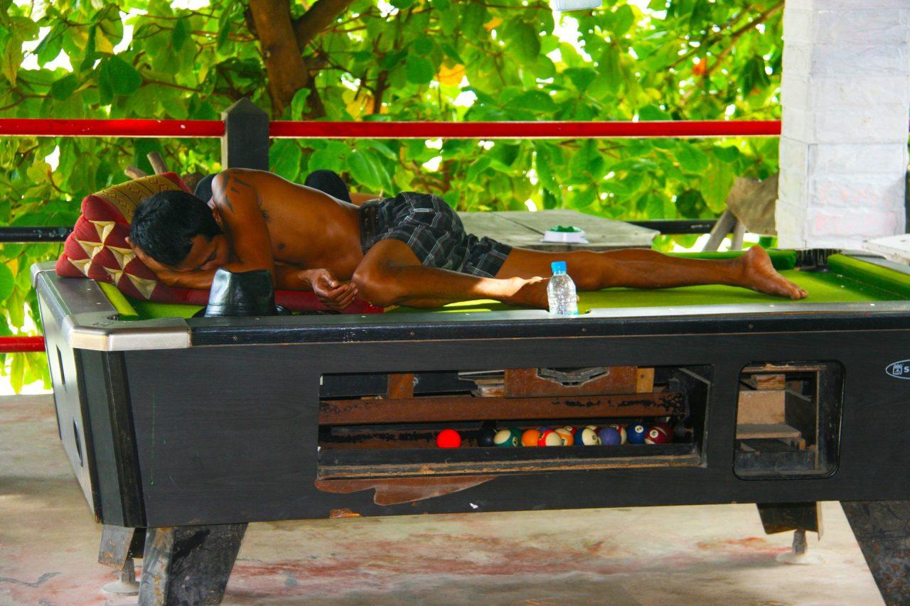 man sleeping on pool table